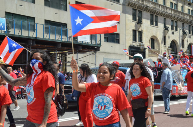 A Young NYDIS Marcher Waves her Flag and Smiles